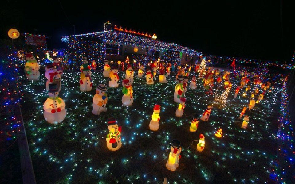 Στολισμένο σπίτι με αυλή γεμάτοι χριστουγεννιάτικους χιονάνθρωπους
