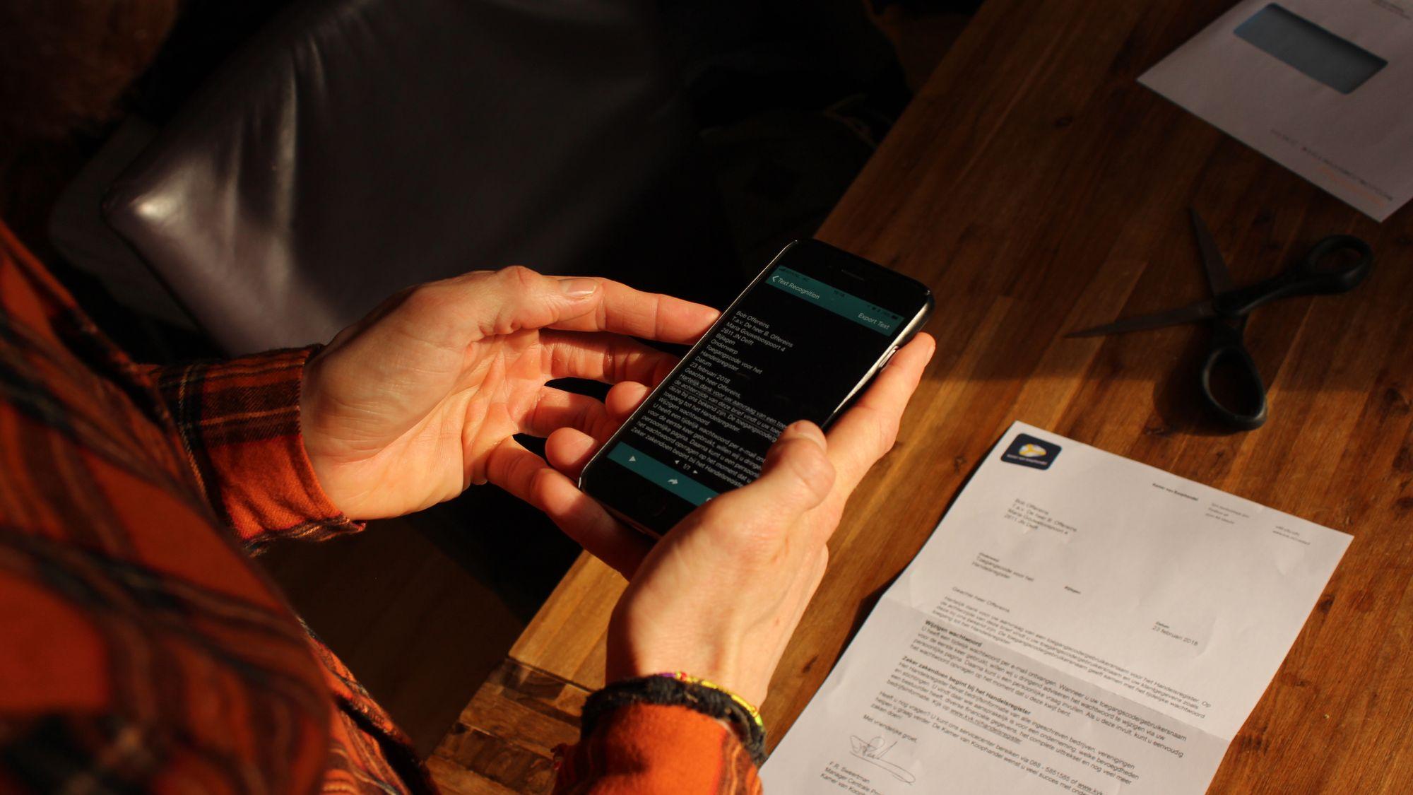 Άνθρωπος κρατάει κινητό και βγάζει φωτογραφία κάποια χαρτιά