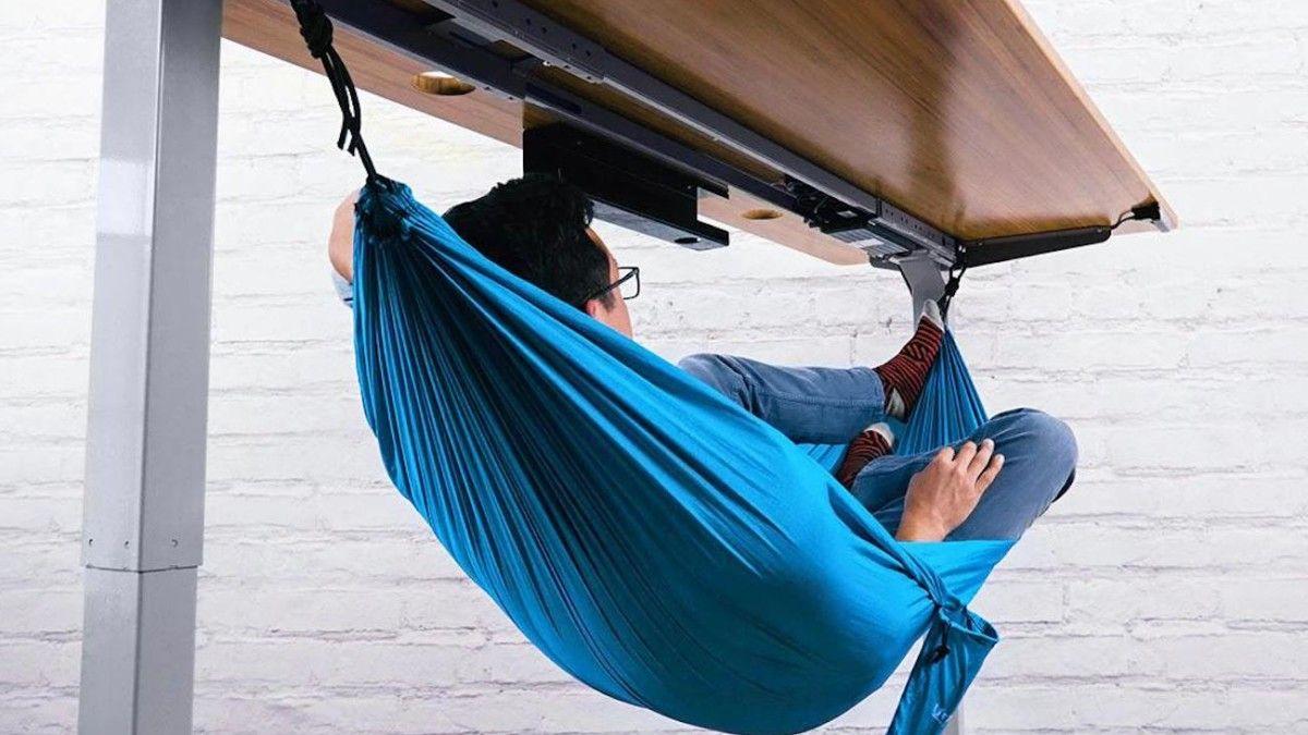 Άνθρωπος που κάθεται σε μια μπλε κούνια η οποία είναι τοποθετημένη κάτω από το γραφείο του