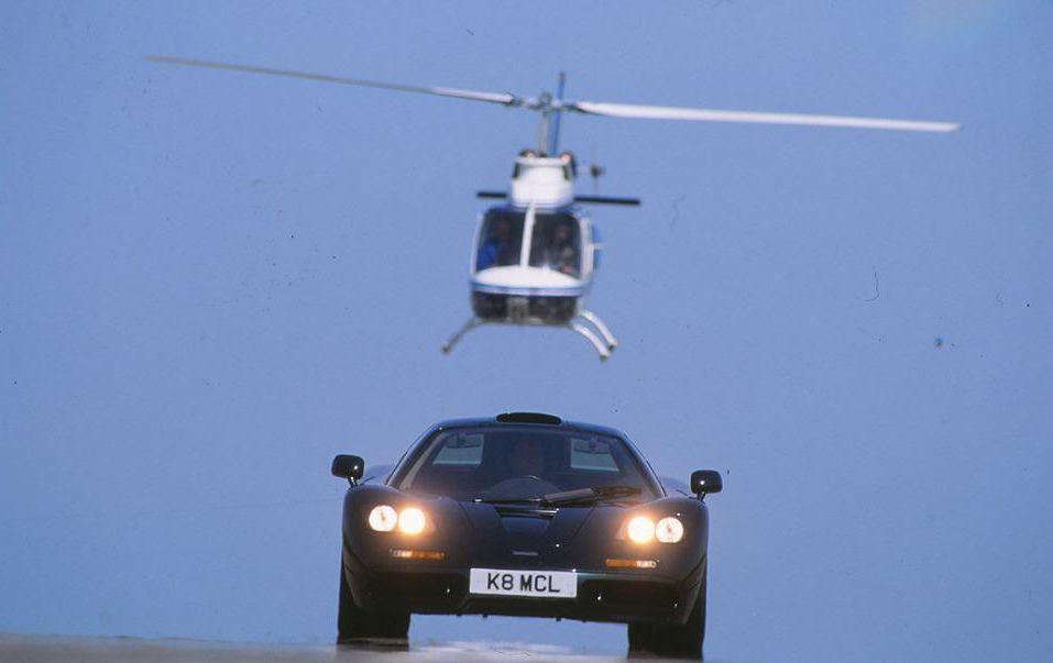 Μια μαύρη McLaren F1 και από πάνω της ένα λευκό ελικόπτερο