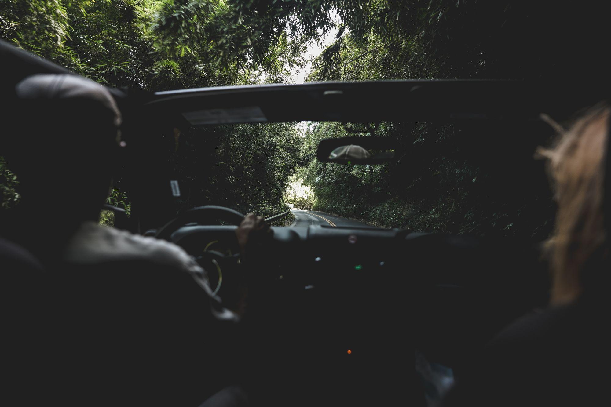 Δύο άνθρωποι μέσα σε κάμπριο αυτοκίνητο σε δρόμο με δέντρα